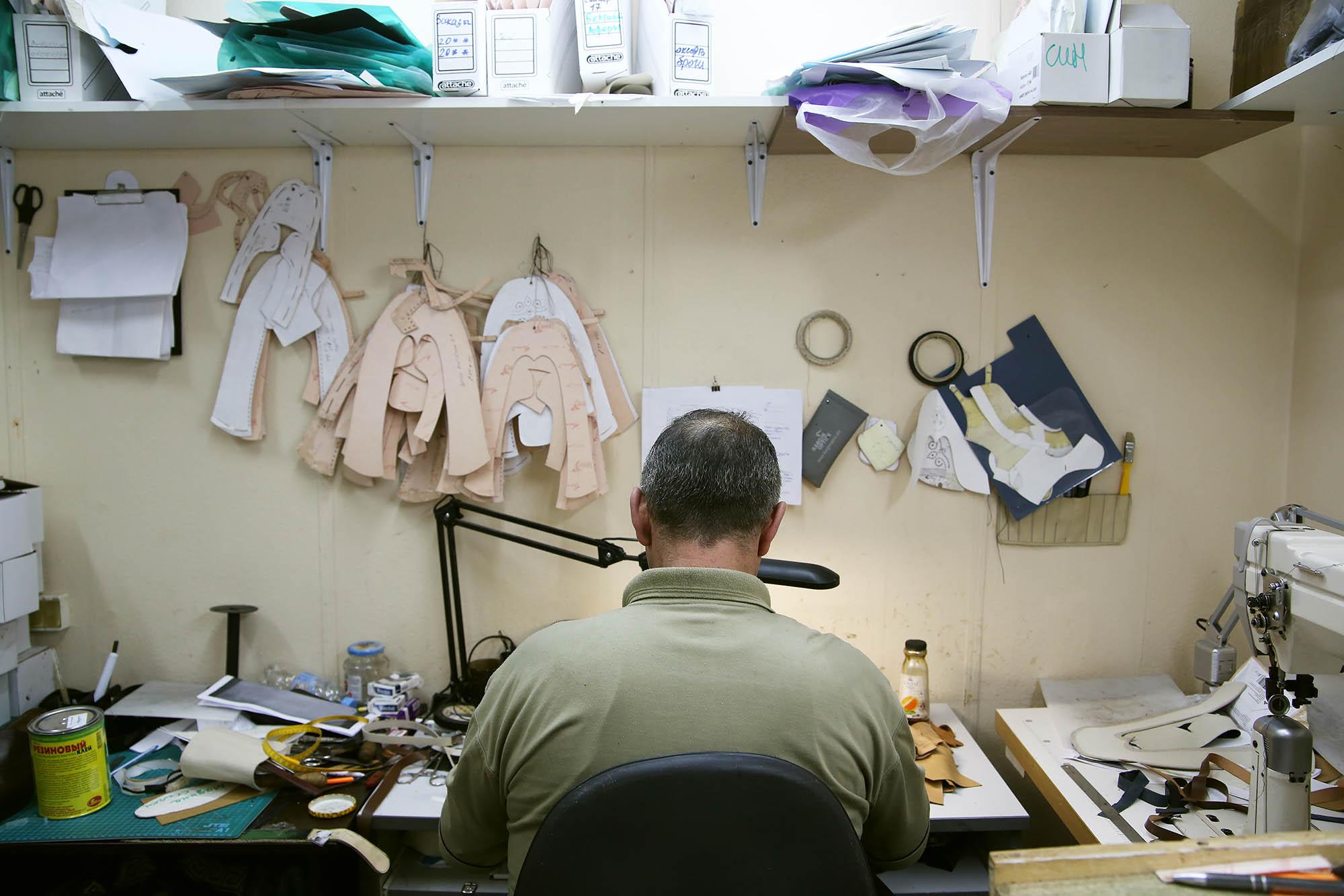 Так выглядит рабочее место в цеху. Мастер делает выкройку для новой пары обуви