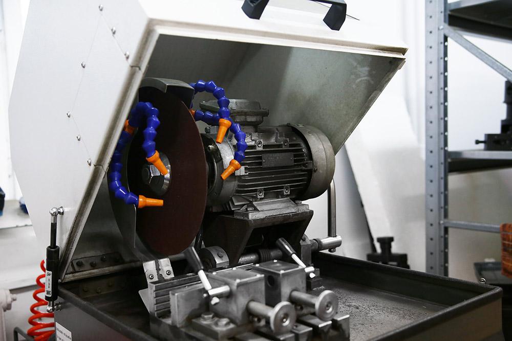 Металлографический отрезной станок нужен, чтобы резать образцы без перегрева металла. Он охлаждает металл водой со специальной эмульсией