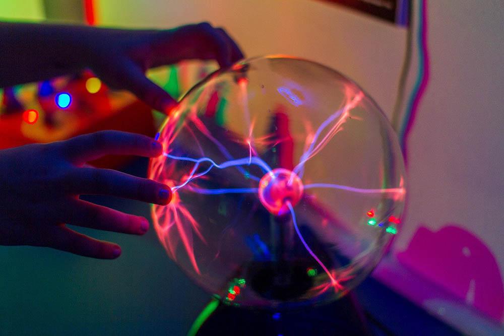 Плазменная лампа с искусственными молниями. В середине находится электрод, а внутри сферы лампы — разреженный газ. Напряжение в парах газа попадает на электрод и формирует плазменные разряды. Когда человек дотрагивается до лампы, они концентрируются в местах, к которым прикоснулись пальцы