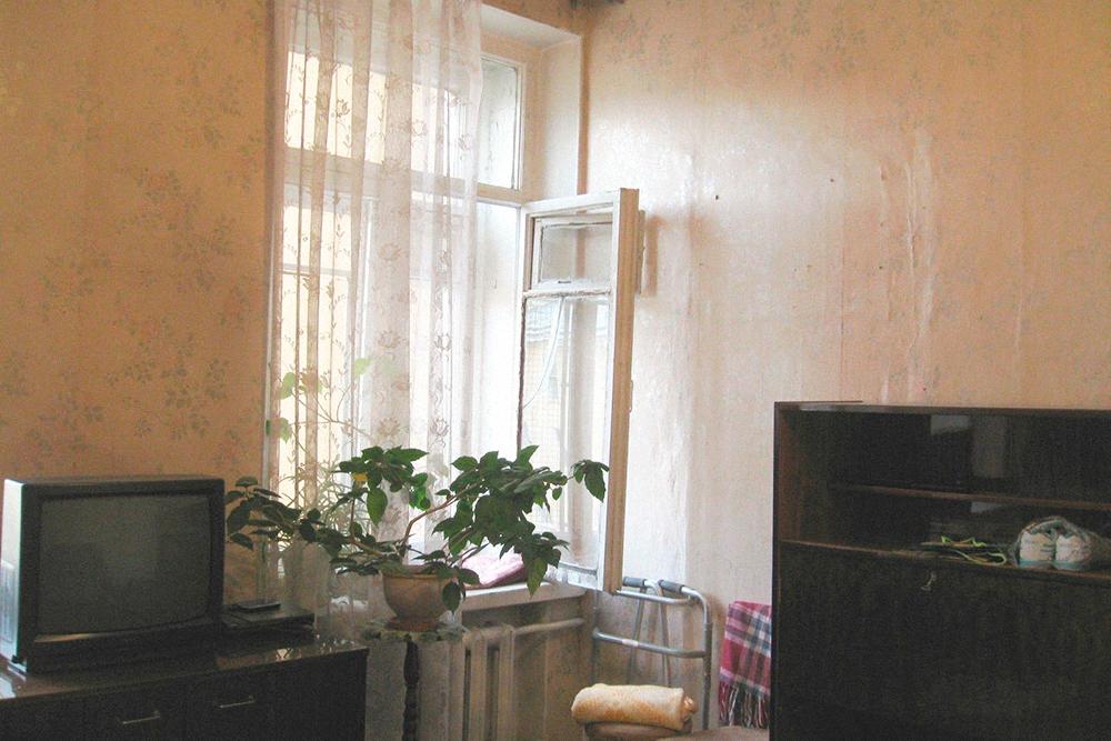 На стене справа сквозь обои проступает дверь в соседнюю комнату. Это особенность дореволюционной планировки — анфилада из комнат. В советские времена такие двери заделывали, когда квартиры становились коммунальными