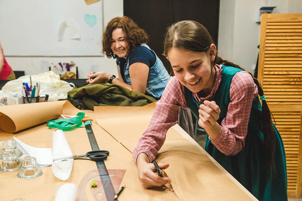 Ученица вырезает готовую выкройку, чтобы потом перенести ее на ткань