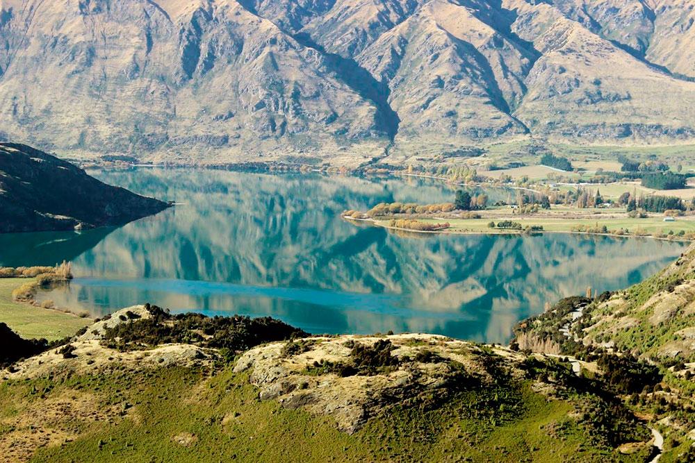 Гладкая поверхность воды озера Ванака отражает окружающие пейзажи
