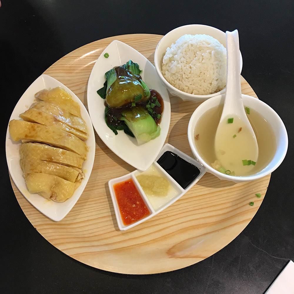 Обычный обед: курица по-хайнаньски с рисом, бульоном, капустой пак-чой и соусами, стоит 80$