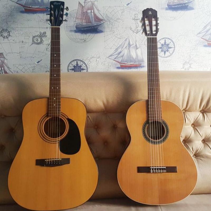 Акустическая гитара Cort — слева. Классическая Alhambra — справа. Визуально они различаются по длине, форме корпуса, ширине грифа и типу колков