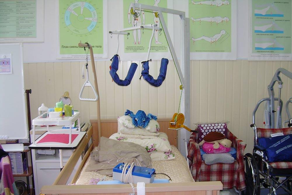 Медицинская мебель. Функциональная кровать оснащена подъемниками, с помощью которых человек может подтягиваться, чтобы сесть или перевернуться. Спинка кровати поднимается. Слева от кровати находится тумбочка, прикроватный столик, а на нем — маленький надкроватный столик. Справа расположено кресло-стул. Кровать стоит так, чтобы подход к инвалиду был с обеих сторон. Такие кровати стоят 20 000—100 000<span class=ruble>Р</span>