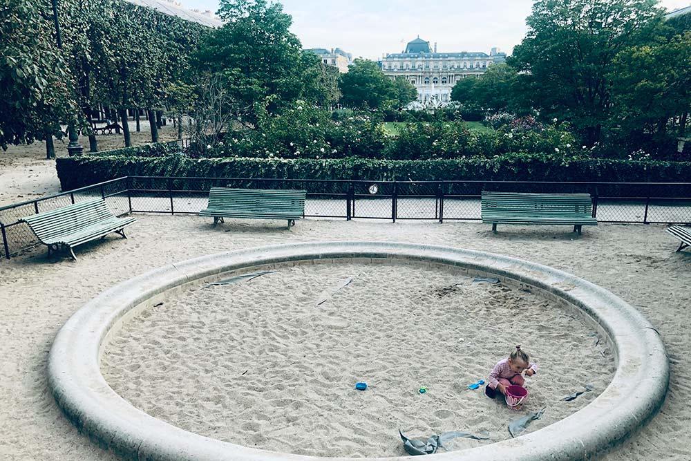 Редкая песочница в центре Парижа, зато с видом на бывший королевский дворец. На фото — дочь Игоря Лея. Она занята тем, что ест песок из ведерка