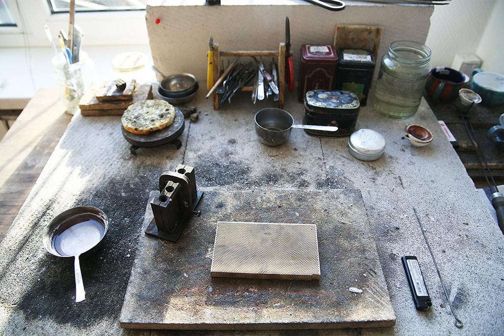 Стол для литья и пайки: на нем работают с горелкой и плавят металл. На столе пинцеты иинструменты для удержания металла. Рядом баночки с материалами для пайки и водой дляохлаждения металла