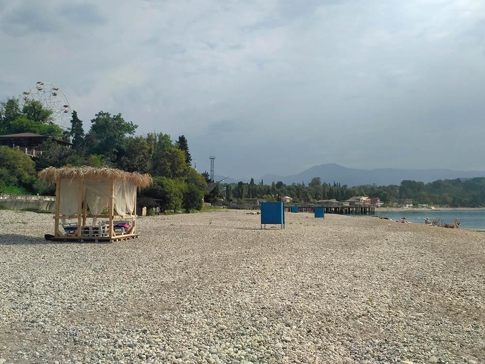 Центральный пляж Гудауты днем в августе. Лежаков нет. Можно лежать на полотенце или сидеть на деревянных поддонах в беседке слева