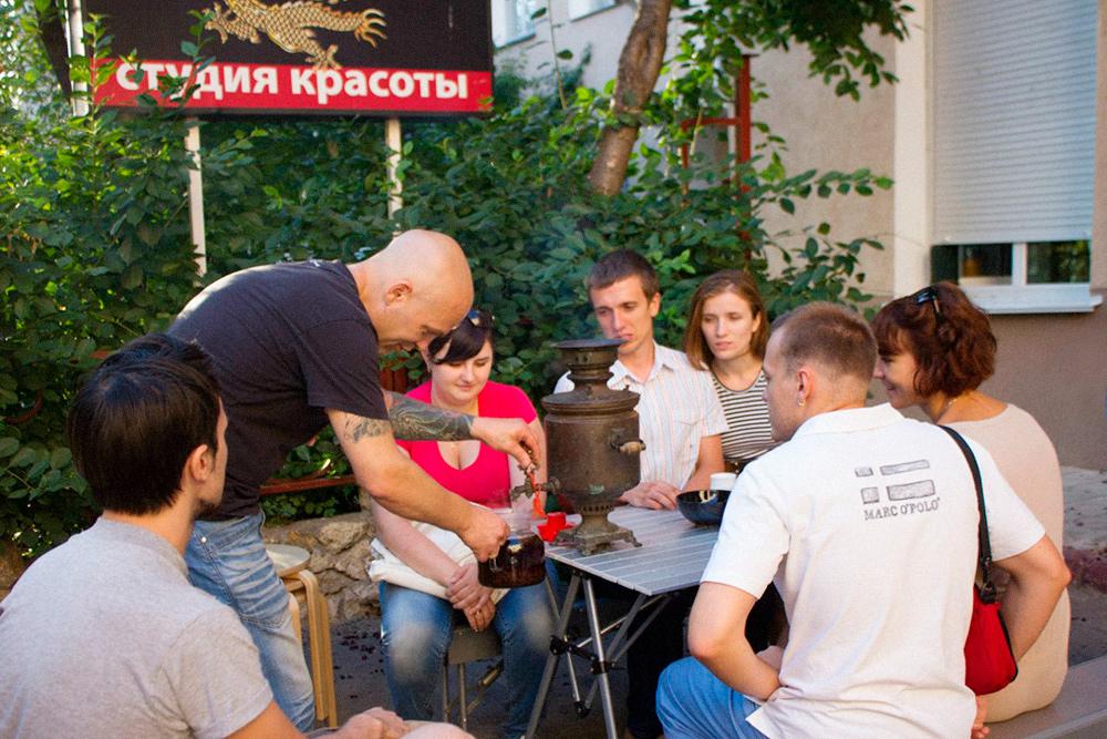 Во дворе перед нашей чайной осваиваю искусство русского чаепития. Самовар настоящий — дровяной