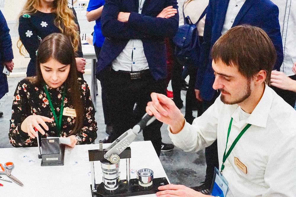 Сотрудники мастерской с помощью вырубщика и пресса делают значки дляпосетителей чемпионата Worldskills