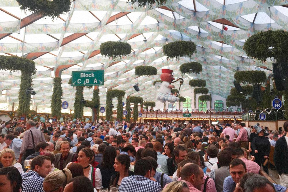 Атмосфера в тенте пивоварни «Хофбройхаус»». Пока не заиграет оркестр, люди сидят на своих местах. Но с первыми аккордами все начнут танцевать