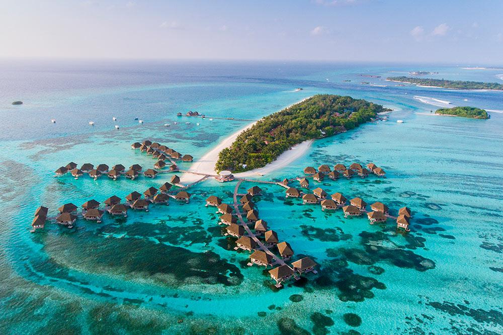Так выглядит типичный остров-резорт на Мальдивах: маленький остров в зелени и с белоснежным песком в окружении океана. Фото: Siraphob Werakijpanich / Shutterstock