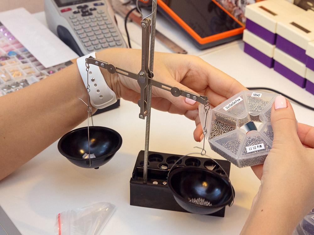 Алина взвешивает бисер для наборов для плетения брошей с помощью ювелирных весов. Поштучно отсчитывать маленькие элементы тяжело