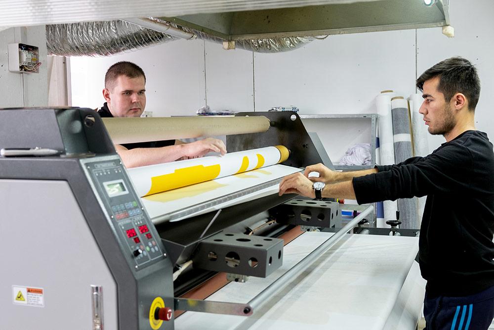 Рабочие переносят рисунок с сублимационной бумаги на ткань через каландр
