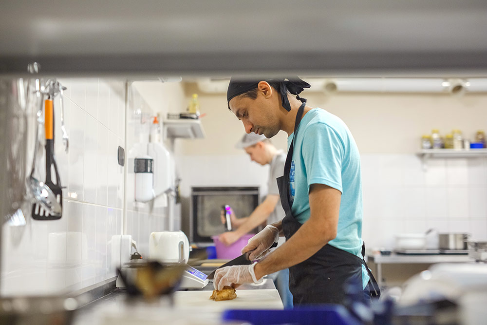 Повар нарезает мясо в блюдо