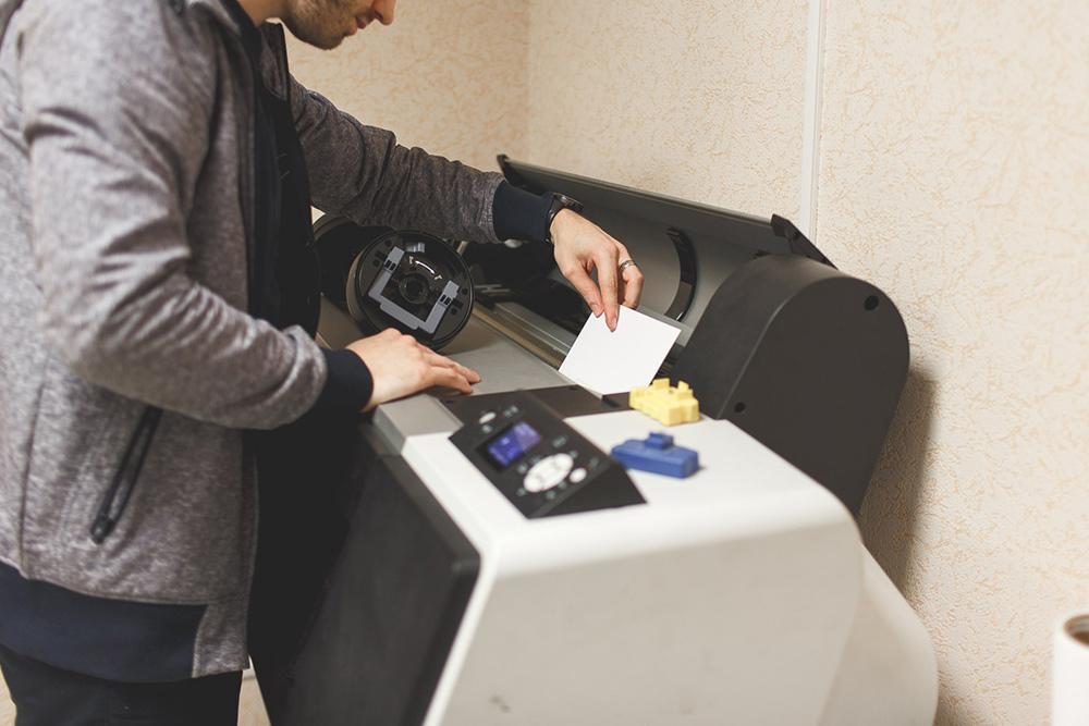Сотрудник Иван за широкоформатным принтером. На нем печатают холсты — фотографии длякниг — в типографии