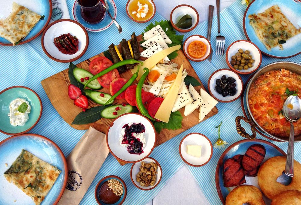 Турецкий завтрак в кафе — 50 ₺ с человека. На фото — местные сыры, овощи, варенье, яичное блюдо менемен, лепешка гезлеме, жареный суджук (вид местной колбасы), сарма (закуска в виноградных листьях), местные пончики пиши