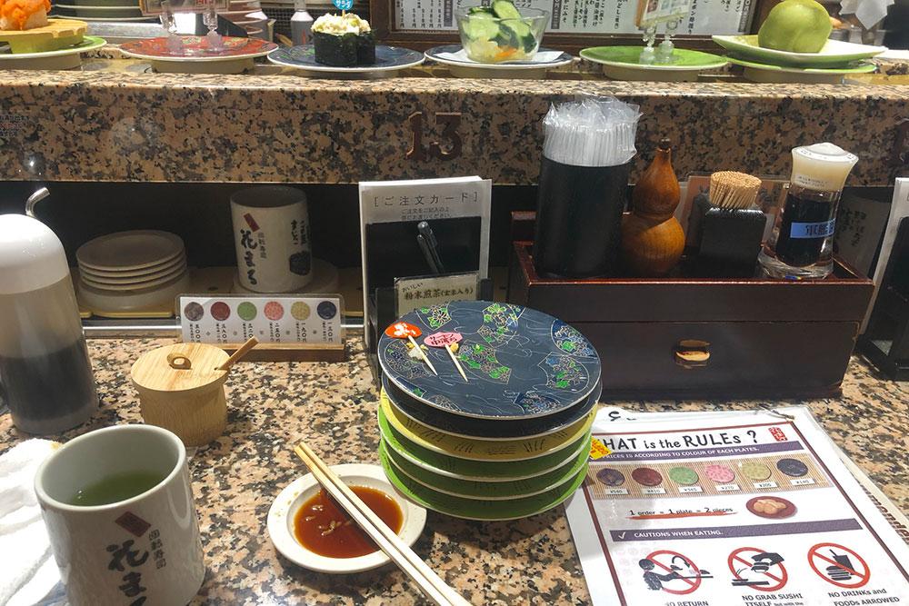 Поужинал в суши-баре с конвейерной лентой. Разные цвета тарелок обозначают разную стоимость блюд