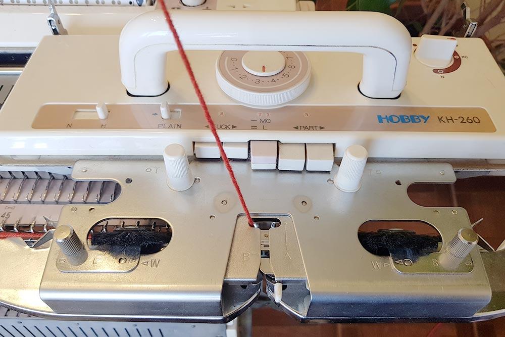 Внитевод каретки заправляется пряжа. Накаретке есть регулятор плотности вязания икнопки, которые включают разные переплетения. Ручка сверху нужна, чтобы двигать каретку вдоль игольницы