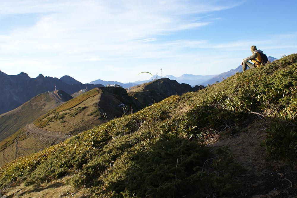 Молодой человек сидит на территории «Розы Хутор» и смотрит на соседний курорт «Альпика». Тудаможно пройти по хребту пешком, но охрана не пустит