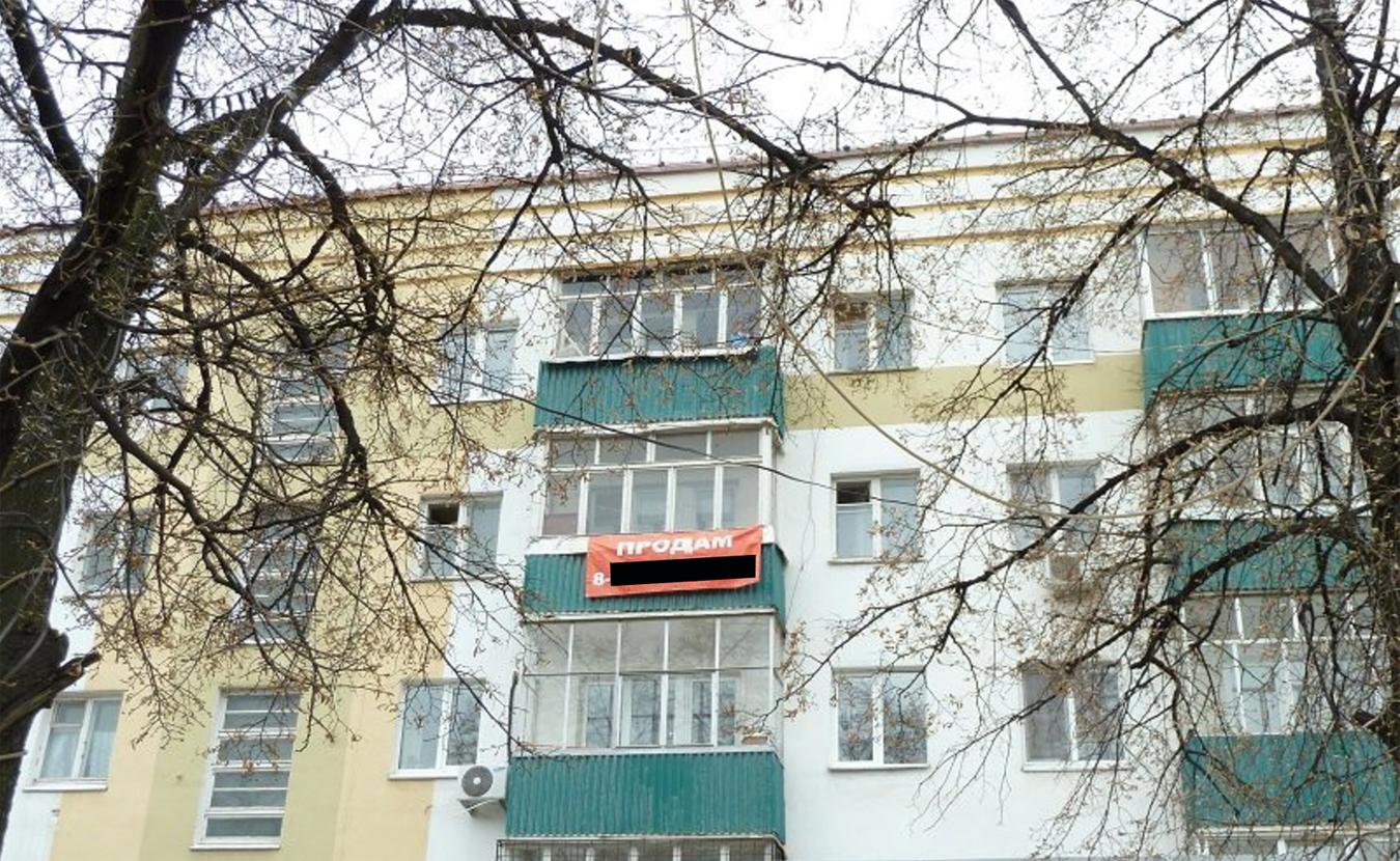 Яркий баннер рассказывает прохожим, что в этом доме продается квартира