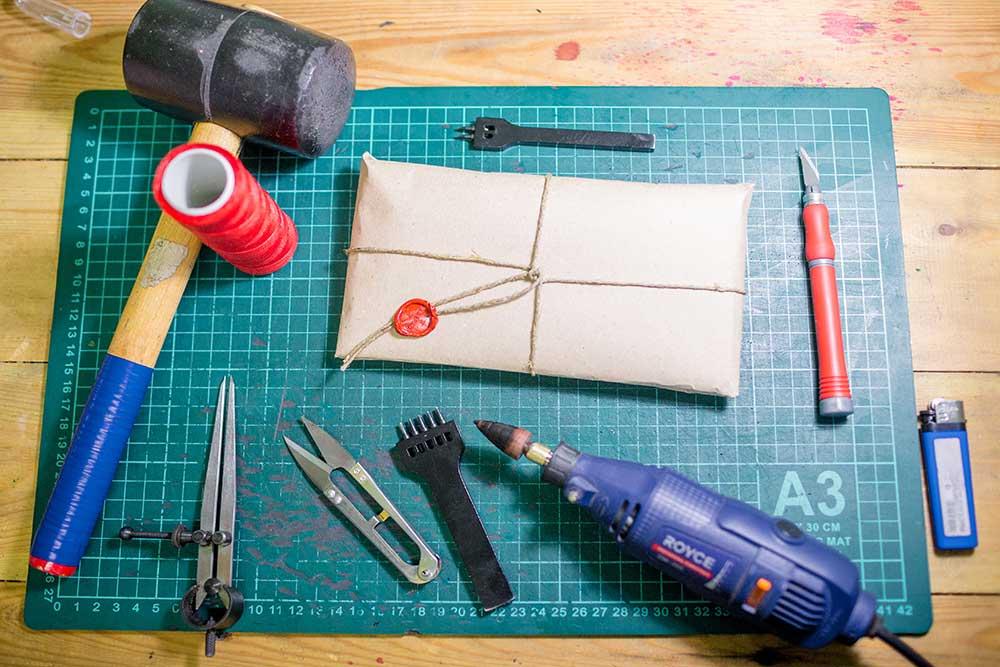 Пример ручного инструмента: пробойники, киянка, портновские ножницы для нитей, раскройный нож, полировальная машинка. Ножи для кожи и расходники для кроя меняют раз в месяц, остальной инструмент — в среднем раз в 9 месяцев