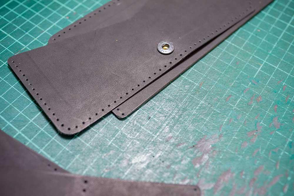 Этапы работы над бумажником. Сначала детали изделия раскраивают. Тут же наносят тиснение или гравировку — на плоской выкройке это сделать легче, чем на готовом изделии