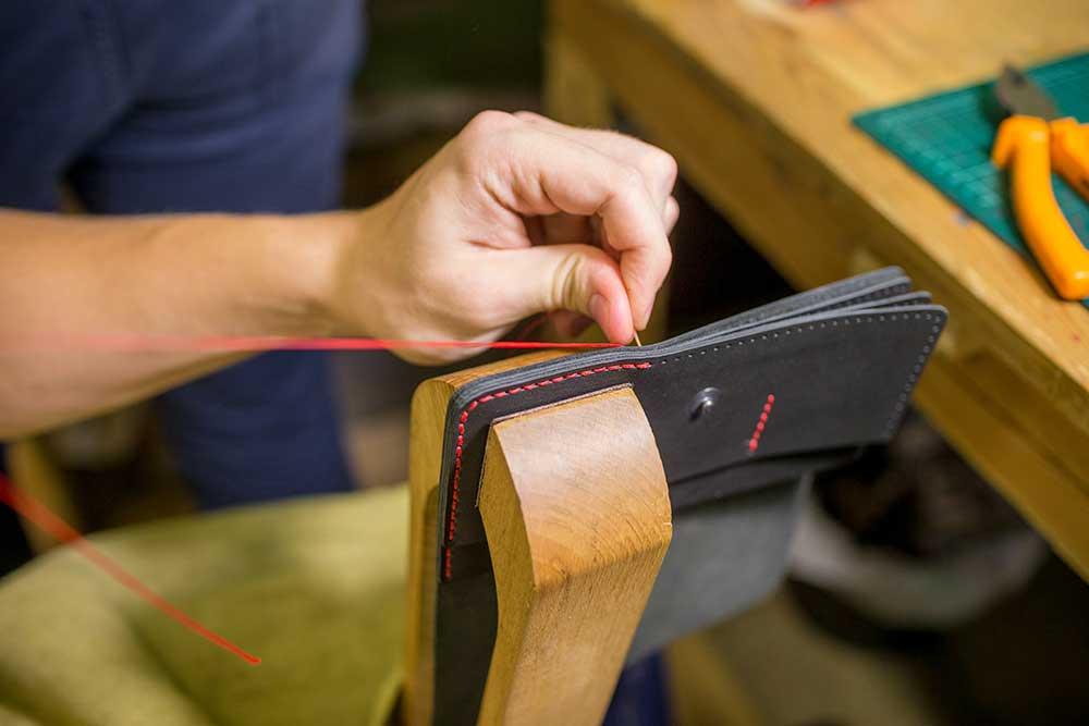 Сшивают детали вместе с помощью шорника — деревянных тисков. Он закрепляется на стол или стул — с ним работать удобнее и быстрее
