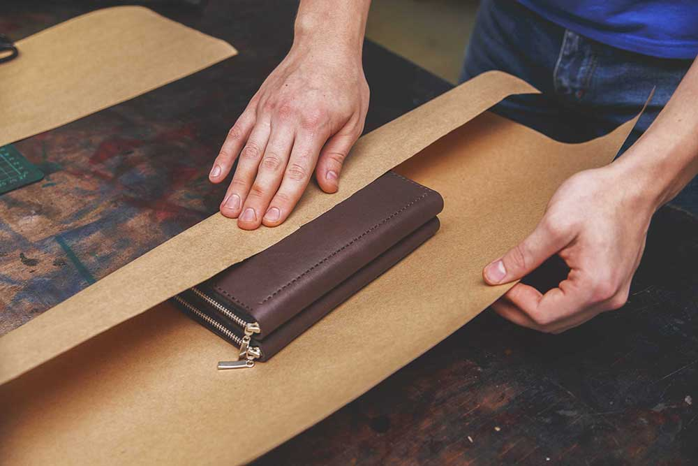 Есть два вида упаковки: базовая из бумаги и подарочная деревянная, которую нужно покупать отдельно. Вместе с изделием в упаковку часто кладут брошюру с рекламой компании, подарок или талон на скидку. На фото последовательность упаковки кошелька вплоть до отправки его на почте