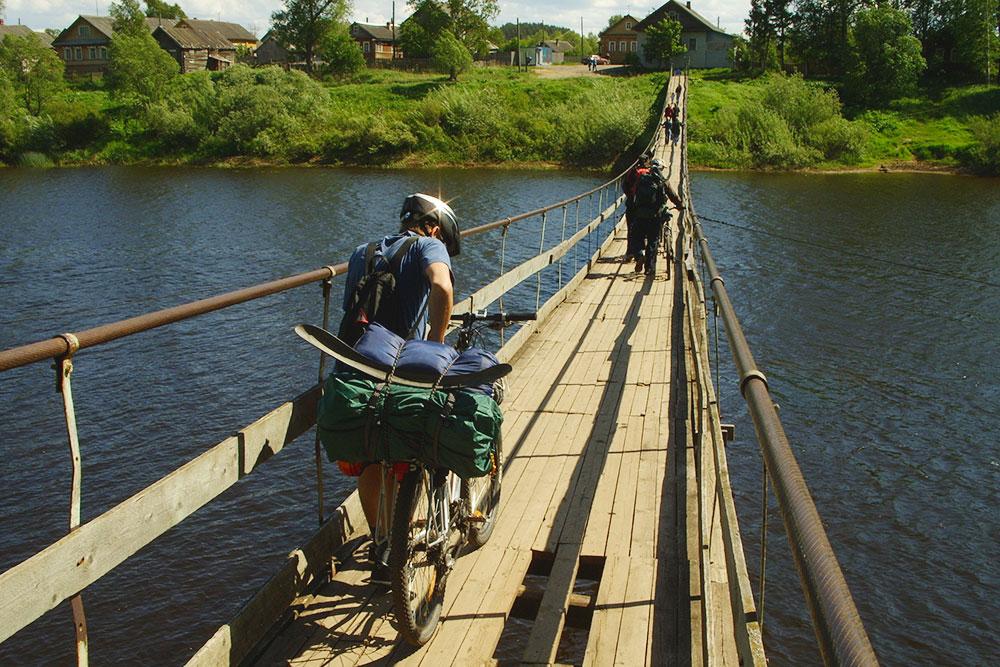 Переход через реку Мсту по навесному мосту в июне 2008 года. Тогда я только начинал кататься на велосипеде и ездил без велорюкзака. Это очень неудобно: приходилось постоянно поправлять сползающий на кочках груз. Если бы поклажа попала в спицы заднего колеса, я мог упасть