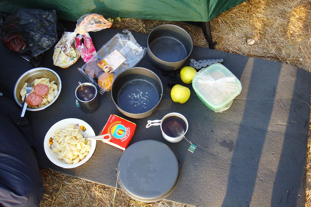Типичный походный ужин: макароны с колбасой, хлеб и сыр. На десерт — чай с кексами и яблоки