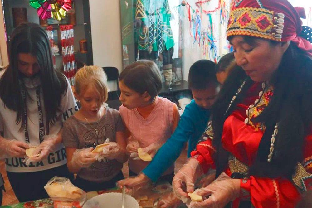 Мастер-класс по лепке шорских пельменей с кедровым орехом. Справа женщина в национальном шорском костюме
