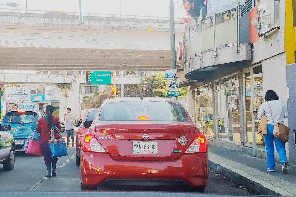 На этом фото сразу два представителя «дорожных рабочих» — на заднем плане жонглирующий парень, а перед ним женщина, торгующая рукодельными сумками