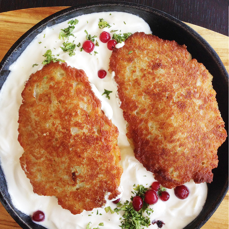 Колдуны подают на чугунной сковороде с большим количеством сметаны, зеленью и ягодами