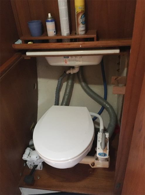 В туалете все смывается за борт или сначала в накопитель — танк серых вод, а из накопителя потом сбрасывается в море. Чтобы смыть жидкость, нужно качать ручку на фото справа. Она напоминает велосипедный насос