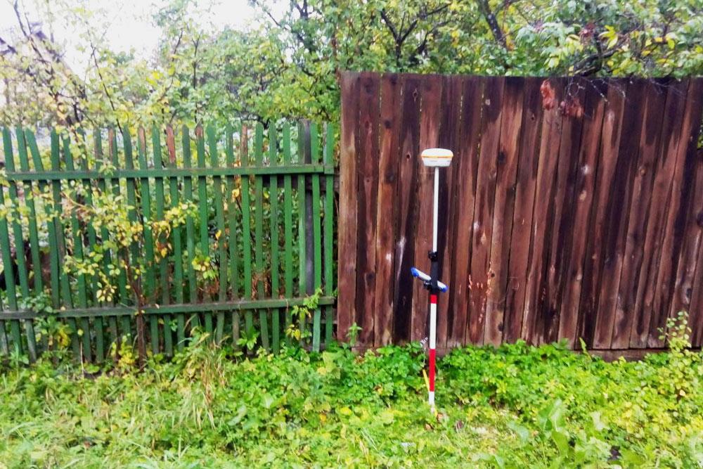 Слева старый забор, а вцентре — аппарат, чтобы проверить координаты наместности