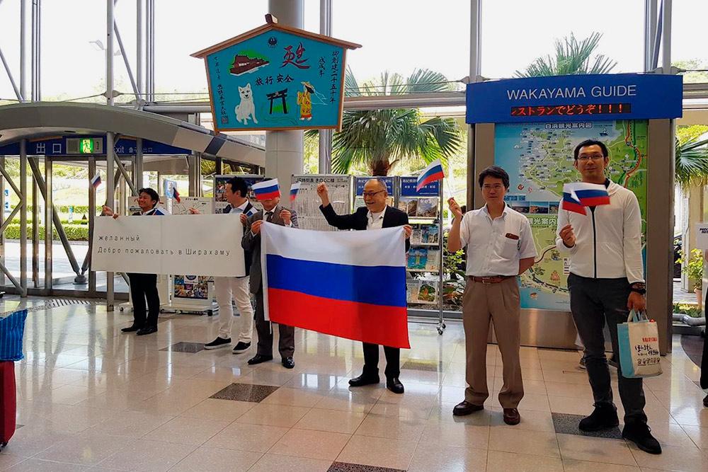 Представители японской префектуры Вакаяма встречают журналистов в аэропорту. На плакате написано: «Желанный. Добро пожаловать в Ширахаму»