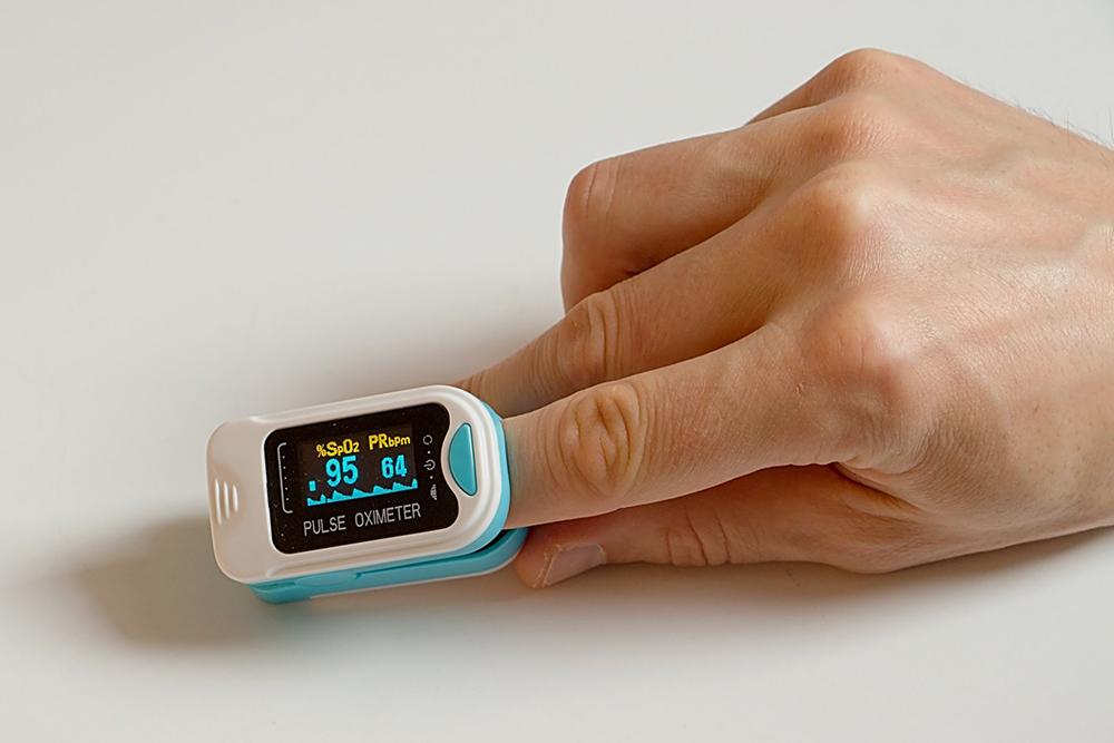На фотографии — пульсоксиметр, предназначенный для измерения SpO2 на пальце. На дисплей выводятся все данные, которые собирает прибор. Источник: health.state.mn.us