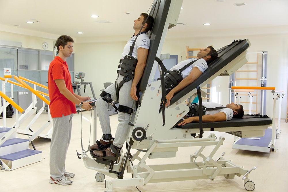 Вертикализатор нужен для пациентов, которые не могут самостоятельно стоять. В положении лежа человека закрепляют на столе, а затем меняют угол наклона. Это нужно, чтобы улучшить кровообращение. Источник: Espana Rusa
