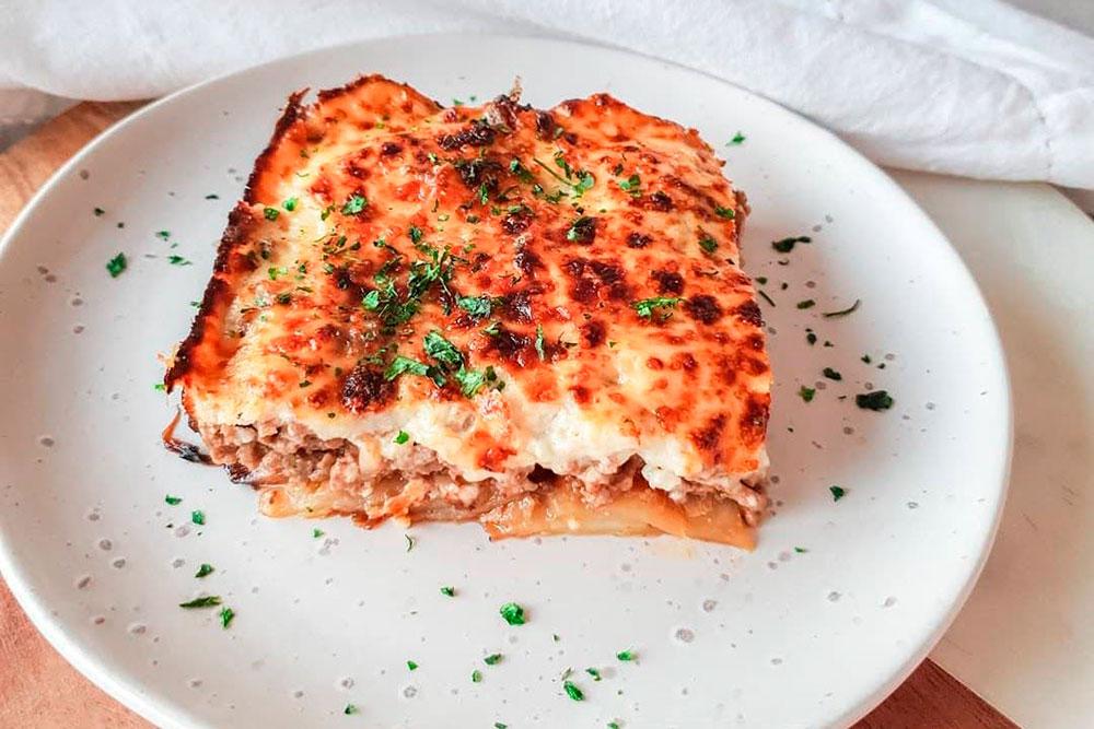 Порция мусаки похожа на кусок слоеного пирога из фарша, картофеля, баклажанов и соуса бешамель. Средняя цена: 7€