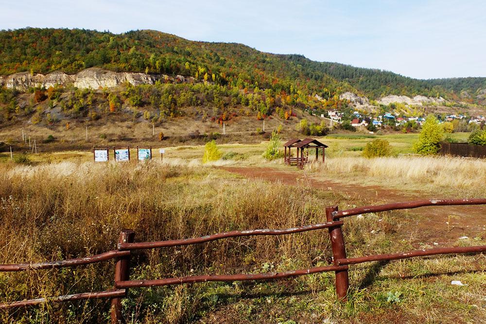 Один из кемпингов на окраине Ширяева: забор, две беседки, кострище и вода в роднике
