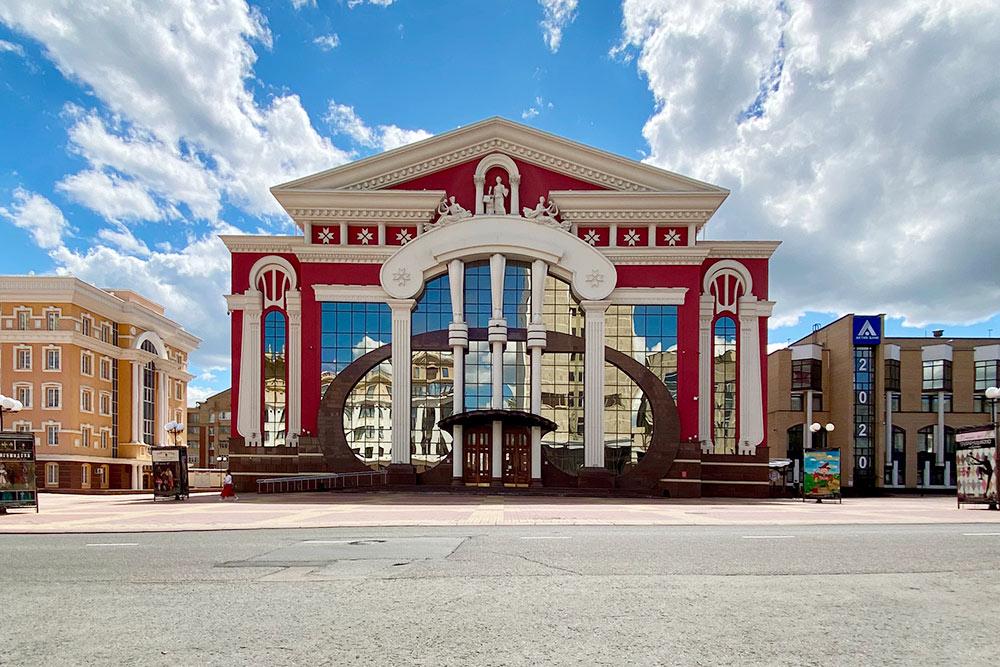 Днем в зеркальном фасаде театра отражается небо и соседние здания, а вечером включается цветная подсветка