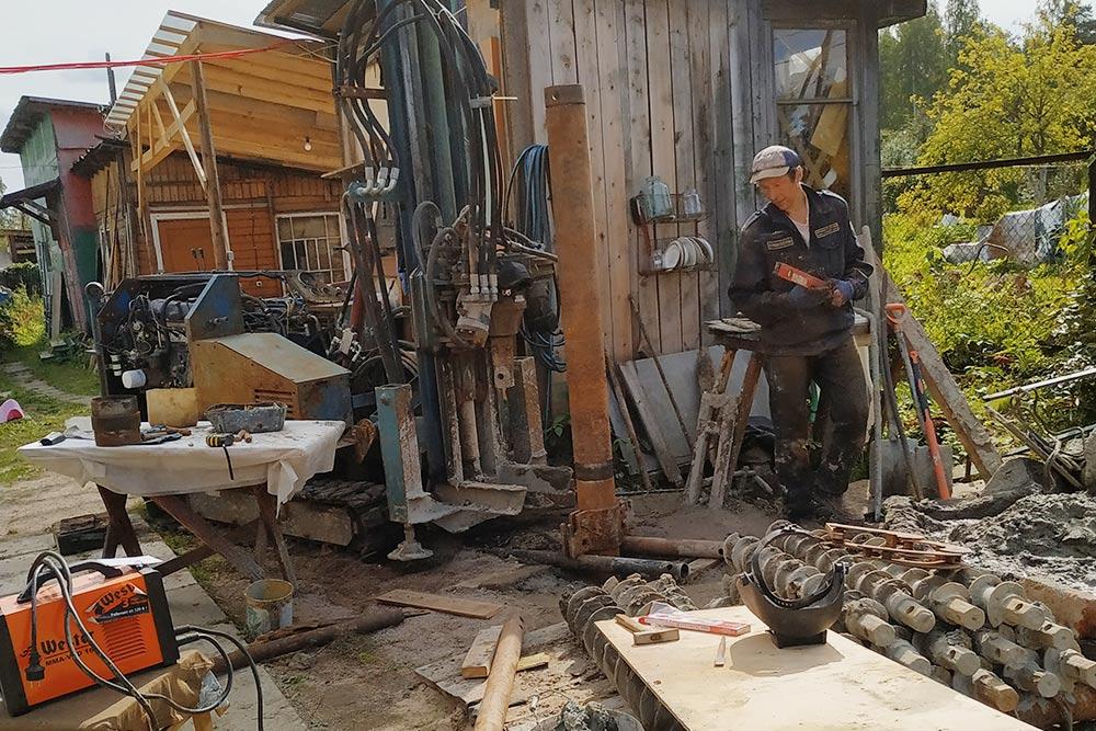 Мы бурили «Аллигатором» — он спрятался на заднем плане фото. Это станок массой 1,8 тонны, длиной 3 м и шириной 1 м. На земле — использованные шнеки, из скважины торчит внешняя обсадная труба, так называемый кондуктор. О нем еще поговорим