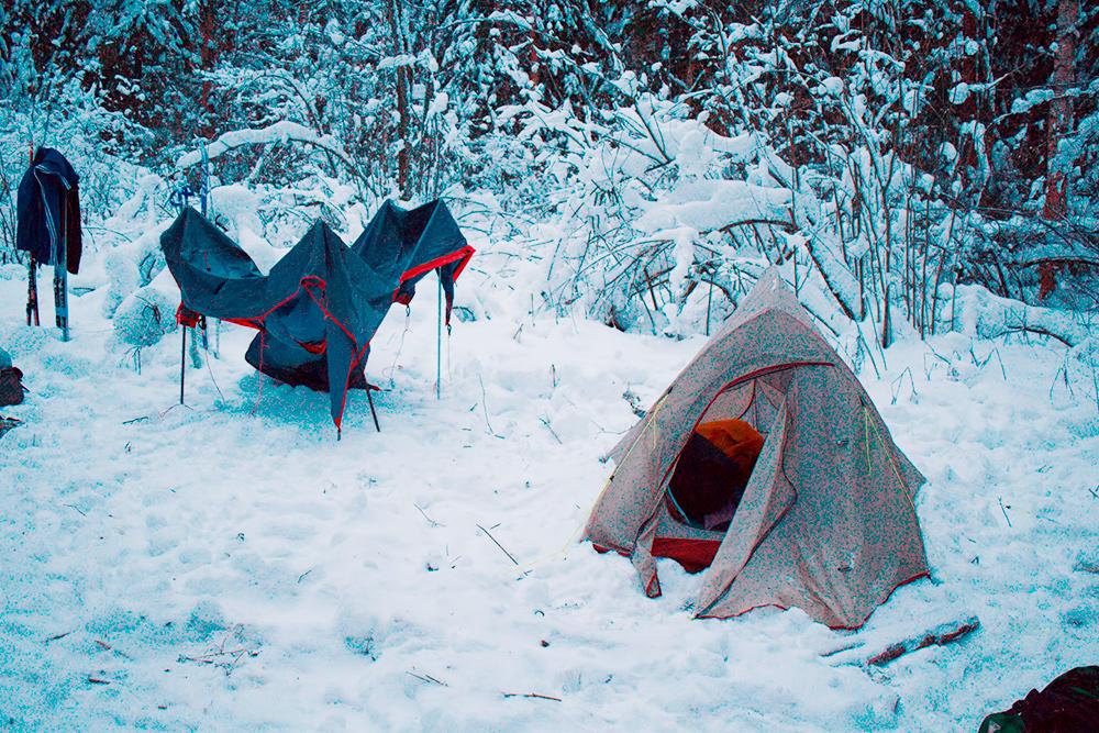 Справа — обычная летняя палатка, вкоторой будем ночевать. Покраям мы присыпали ее снегом, чтобы незадувал ветер. Назаднем плане сушим тент
