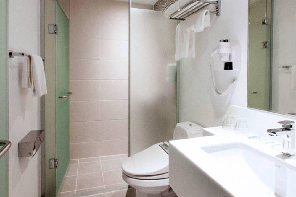 Ванная комната в номере отеля Holiday Inn Express Seoul Euljiro. Там стоит «умный унитаз» с кучей кнопок и пояснениями на корейском языке. Опробовать все его функции мы так и не решились