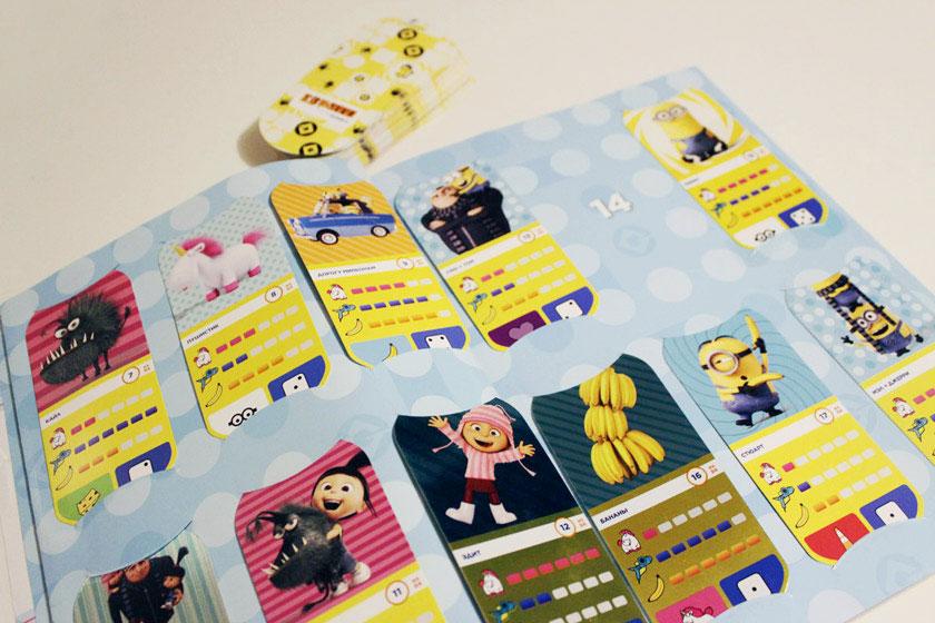 Альбом для миньонов с прорезями для карточек, правилами игры и игровым полем. На заднем плане — стопка «повторок»