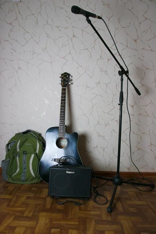 Инструмент и аппарат уличного музыканта Вовы: гитара, переносной усилитель, рюкзак для него, микрофон со стойкой
