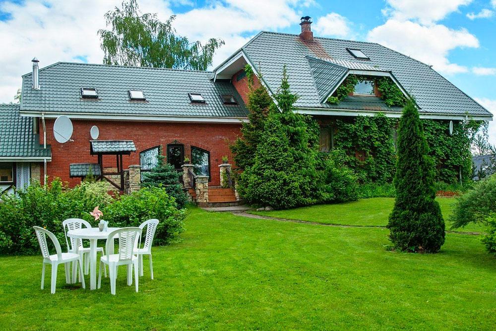 Дом поделен на 2 части: на переднем плане гостевая часть с террасой, за елочками — территория хозяев