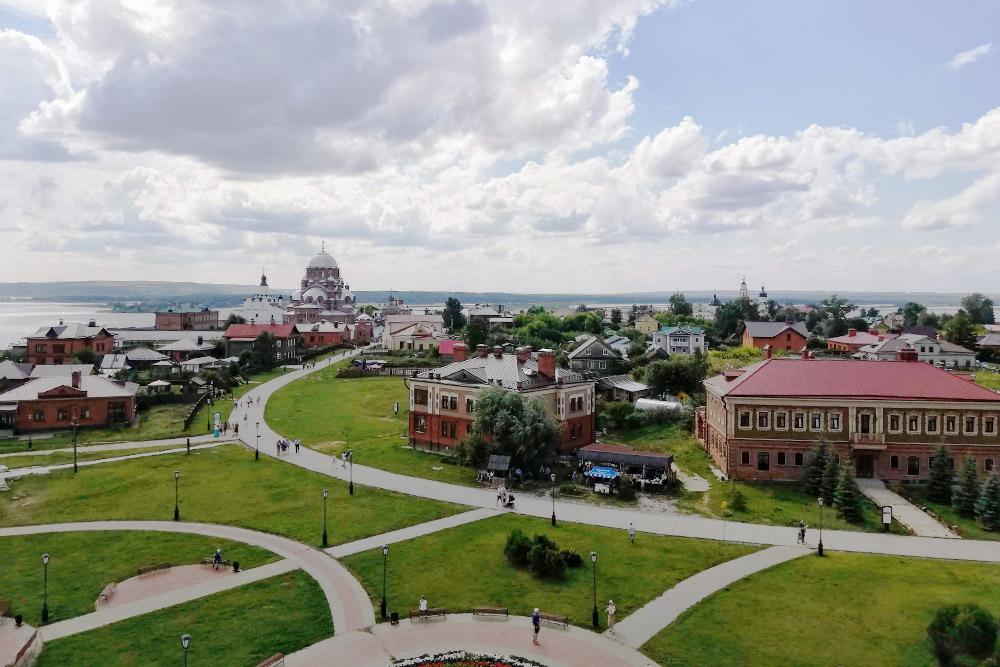 Здание скрасной крышей напереднем плане— гостиница «Дом купца Каменева». Назаднем плане— Иоанно-Предтеченский монастырь