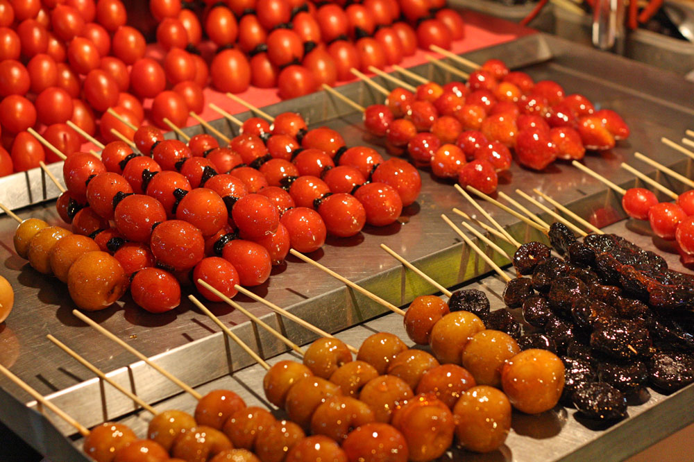 Отдельная экзотика — попробовать еду, которой торгуют на ночных рынках. Слева помидоры, справа клубника, снизу яблоки — все это в карамели